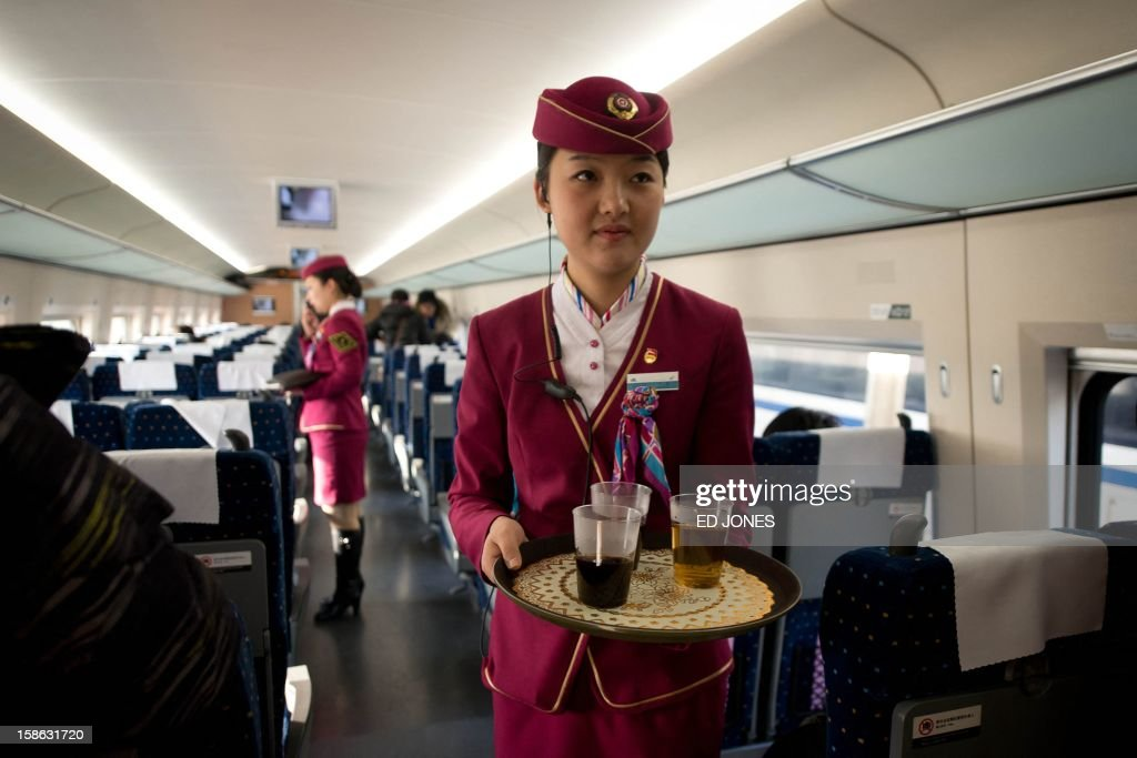 A stewardess carries tea for journalists aboard a high-speed train in Hebei province south of Beijing on December 22, 2012. China showed off the final link of the world's longest high-speed rail route, set to open on December 26, stretching from Beijing to the southern Chinese city of Guangzhou. Travelling at around 300 kph, trains on the new route are expected to cover the 2,298-kilometre (1,425-mile) journey in a third of the current time from 22 hours to eight. AFP PHOTO / Ed Jones
