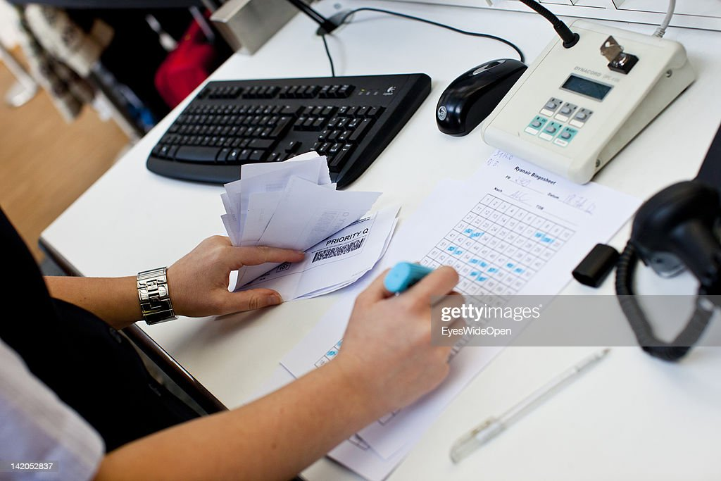Stewardess controls airline tickets with priority and normal status at check-in or departure for a RyanAir flight at Allgaeu Airport on February 18, 2012 in Memmingen, Germany.
