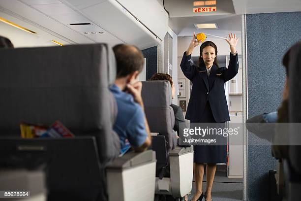 Stewardess explaining safety procedures to passengers on airplane