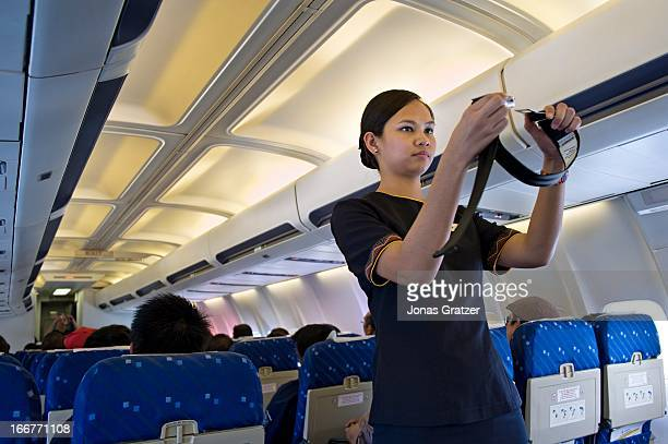 A stewardess gives a safety procedures demonstration on board an Air Philippines plane