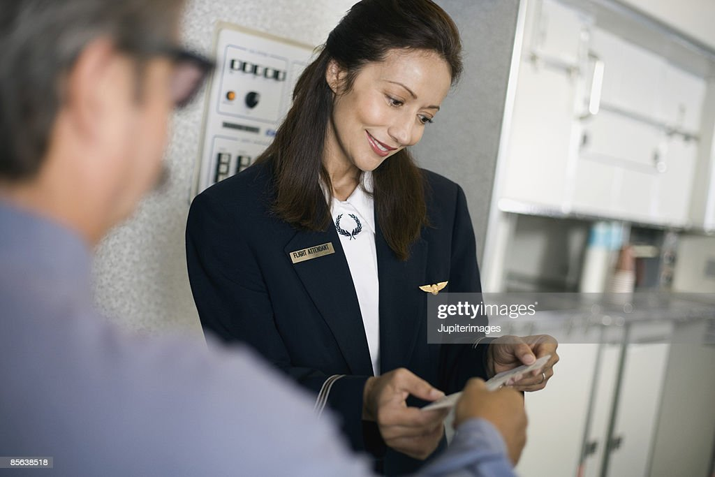 Stewardess greeting passengers on airplane