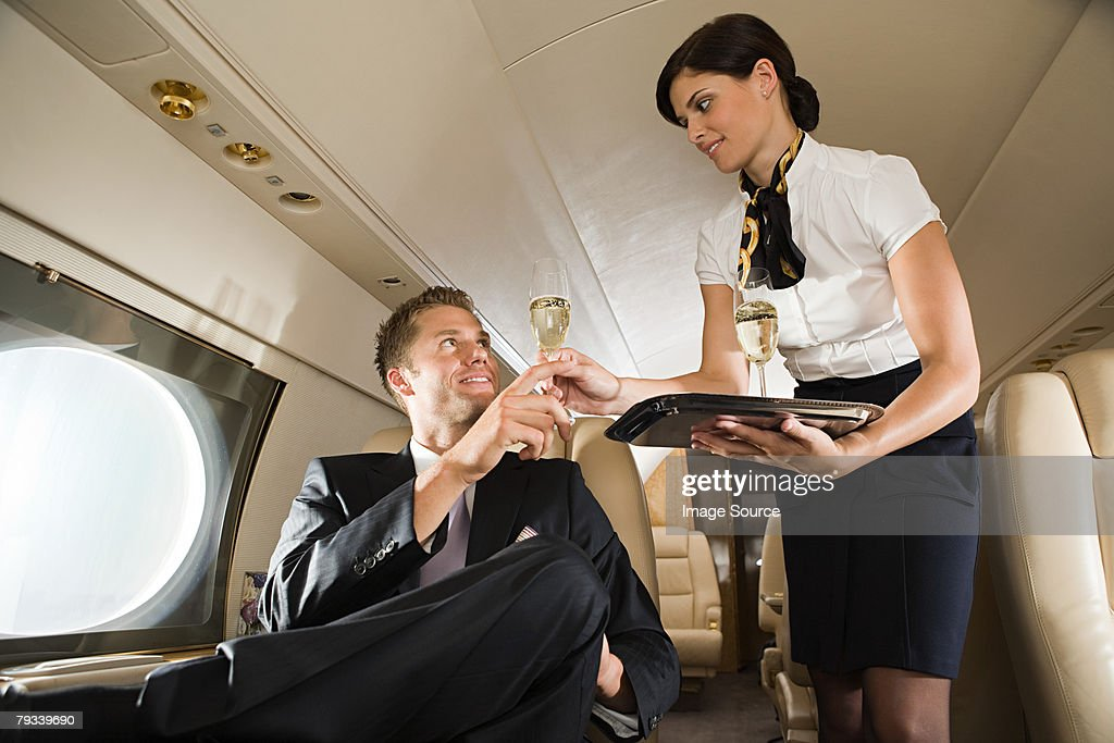 Stewardess handing champagne to man : Stock Photo