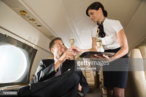 Stewardess handing champagne to man : Foto de stock
