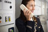 Stewardess instructing passengers on airplane over the loudspeaker