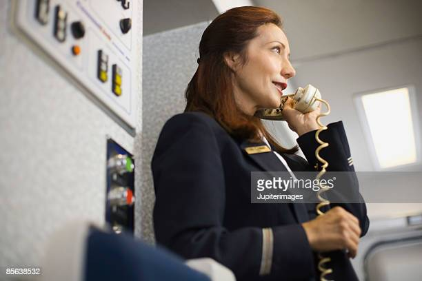Stewardess instructing passengers on airplane over the loudspeaker