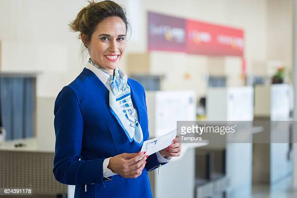 Stewardess looking at camera and holding a boarding pass