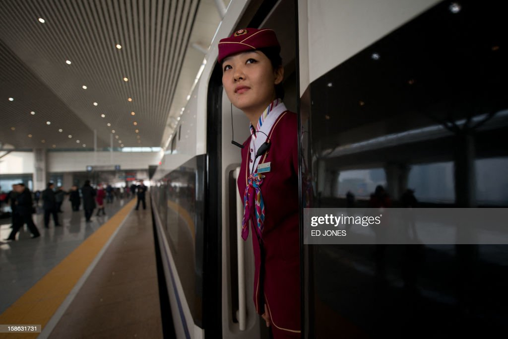 A stewardess looks out from the doorway of a high-speed train in Hebei province south of Beijing on December 22, 2012. China showed off the final link of the world's longest high-speed rail route, set to open on December 26, stretching from Beijing to the southern Chinese city of Guangzhou. Travelling at around 300 kph, trains on the new route are expected to cover the 2,298-kilometre (1,425-mile) journey in a third of the current time from 22 hours to eight. AFP PHOTO / Ed Jones