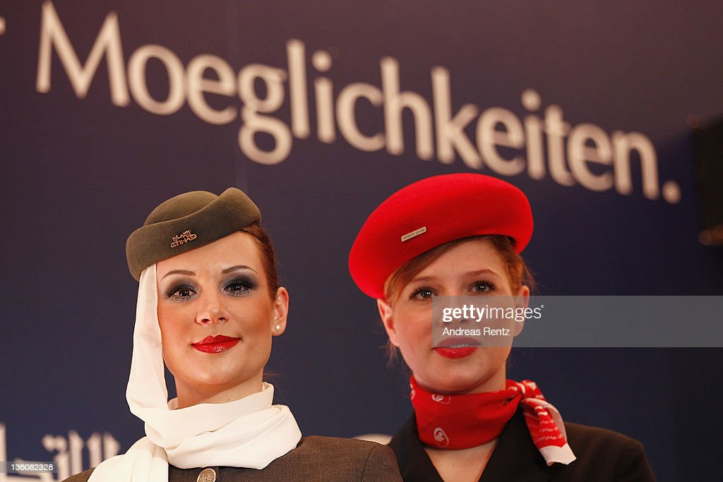 A stewardess of Etihad Airways and a stewardess of German airline Airberlin look on during a press conference on December 19, 2011 in Berlin, Germany. Airberlin and Ethihad Airways announced their strategic partnership. Etihad Airways increase its stake in airberlin to 29 per cent and becomes biggest single shareholder in airberlin.