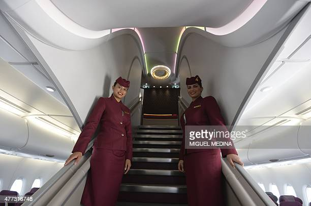 Stewardess of Qatar Airways stand on the inside stairs of an Airbus A380 at Le Bourget airport on June 16 north of Paris on the second day of the...