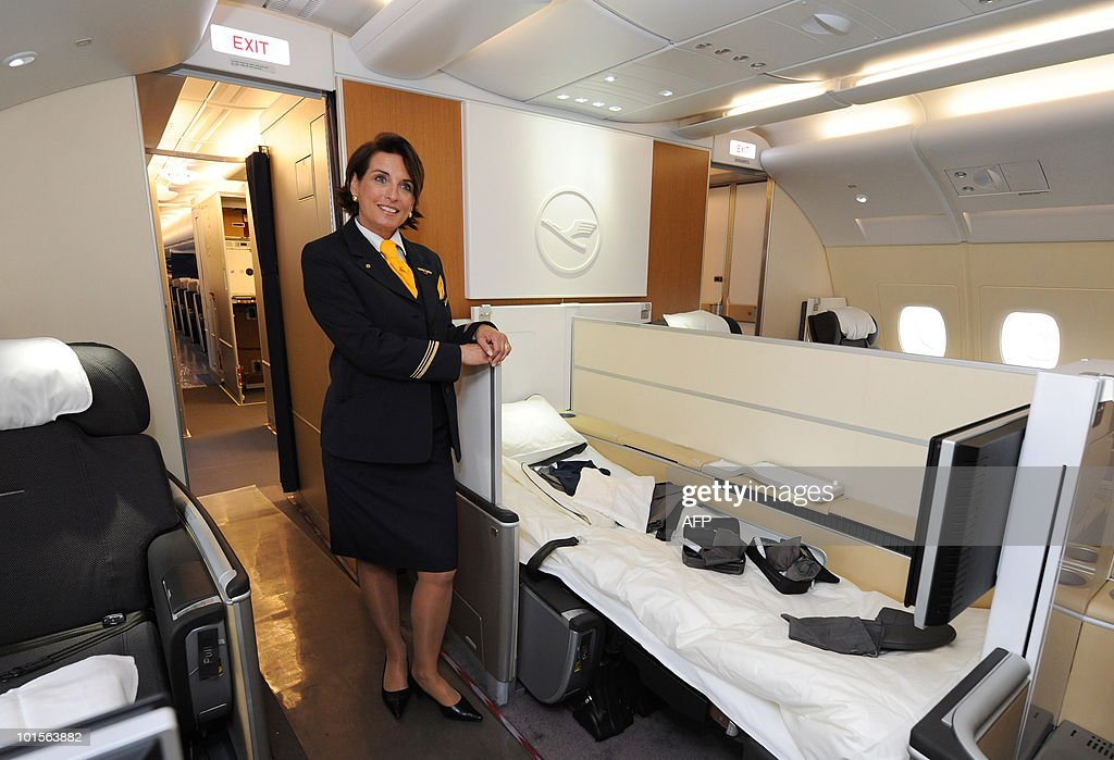 A stewardess poses beside a first class bed of the new airplane Airbus A380 of the German airline Lufthansa during the test landing at the Franz-Josef-Strauss airport in Munich June 2, 2010. The A380 currently tours German airports practicing landing and take-off.