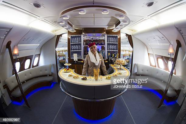 A stewardess poses in the bar of the business class of an Airbus A380 from Emirates airlines during the International Air Show ILA in Schoenefeld...