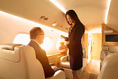 Stewardess serving passenger on private jet