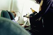 Stewardess serving wine to young business traveller