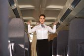 Stewardess standing in aisle of airplane