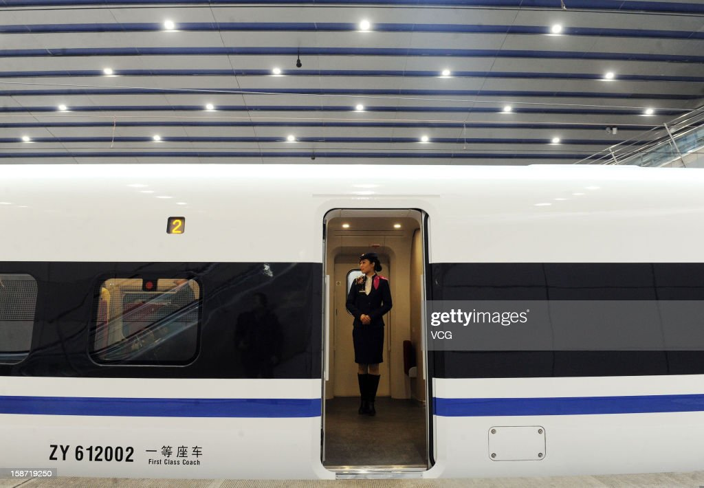 A stewardess stands at a doorway of a CRH high-speed train at Beijing West Railway Station on December 26, 2012 in Beijing, China. The world's longest high-speed rail route linking Beijing and Guangzhou started operation on Wednesday. Running at an average speed of 300 kilometers per hour, the 2,298-kilometer new route will cut the travel time between Beijing and Guangzhou from more than 20 hours to around eight.