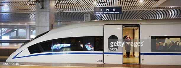 A stewardess stands at a doorway of a CRH highspeed train at Changsha South Railway Station on December 26 2012 in Changsha China The world's longest...