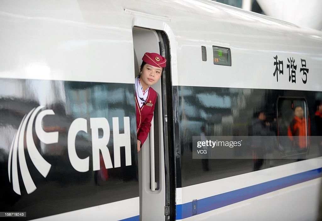 A stewardess stands at a doorway of a CRH high-speed train at Guangzhou South Railway Station on December 26, 2012 in Guangzhou, China. The world's longest high-speed rail route linking Beijing and Guangzhou started operation on Wednesday. Running at an average speed of 300 kilometers per hour, the 2,298-kilometer new route will cut the travel time between Beijing and Guangzhou from more than 20 hours to around eight.