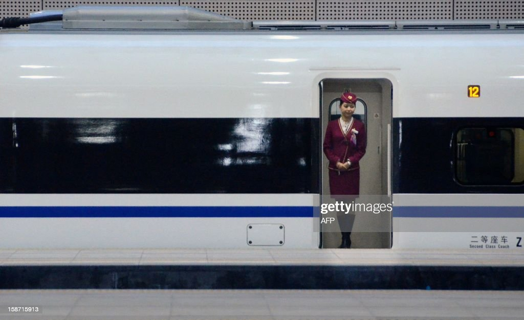 A stewardess stands at the entrance of a high-speed train running from the Beijing to Guangzhou, south China's Guangdong province, at the Beijing west railway station in Beijing on December 26, 2012. China on December 26 started service on the world's longest high-speed rail route, the latest milestone in the country's rapid and sometimes troubled super fast rail network.