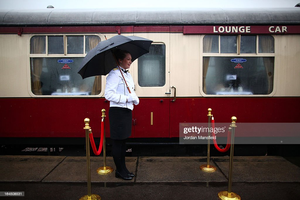 A stewardess waits by a carriage of the Grinsteade Belle ahead of its maiden trip to East Grinstead on March 23, 2013 in Uckfield, England.The Bluebell Railway ran its first steam train this weekend on the reclaimed line from Kingscote to East Grinstead after volunteers from the Bluebell Society worked to reopen the line after its closure on March 17, 1958. 50 years on from Dr. Richard Beeching's report signaling the widespread closure of rural rail routes across the UK, Britain's railways are in great demand with old lines reopening and pressure on to restore rural lines that were closed.