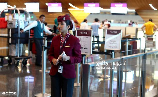 A stewardess waits for passengers at the checkin area in the Hamad International Airport in the Qatari capital Doha on June 12 2017 Qatar Airways...