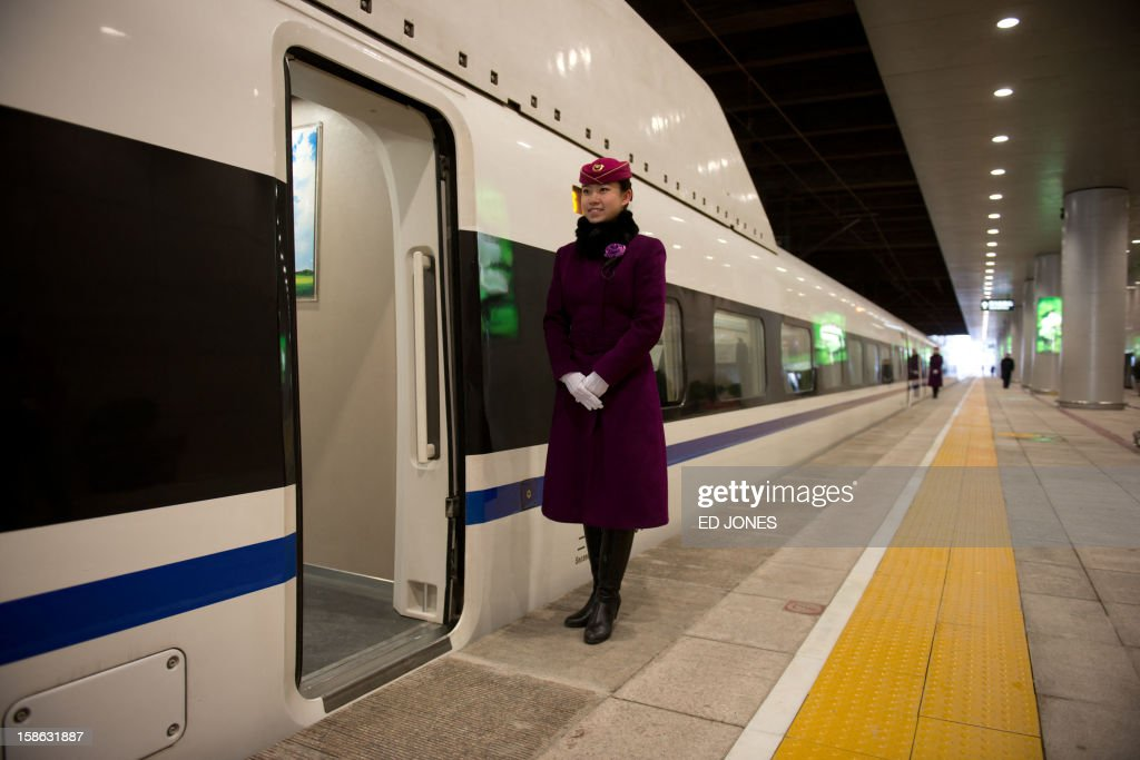 A stewardess waits to greet journalists boarding a high-speed train at the Beijing West Railway Station in Beijing on December 22, 2012. China showed off the final link of the world's longest high-speed rail route, set to open on December 26, stretching from Beijing to the southern Chinese city of Guangzhou. Travelling at around 300 kph, trains on the new route are expected to cover the 2,298-kilometre (1,425-mile) journey in a third of the current time from 22 hours to eight. AFP PHOTO / Ed Jones