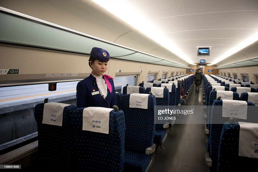 A stewardess waits to serve journalists aboard a high-speed train at the Beijing West Railway Station in Beijing on December 22, 2012. China showed off the final link of the world's longest high-speed rail route, set to open on December 26, stretching from Beijing to the southern Chinese city of Guangzhou. Travelling at around 300 kph, trains on the new route are expected to cover the 2,298-kilometre (1,425-mile) journey in a third of the current time from 22 hours to eight. AFP PHOTO / Ed Jones