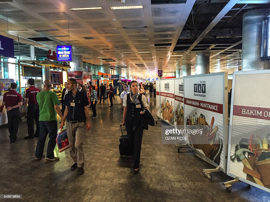 A stewardess (C) walks by the damaged area (R) at Ataturk airport's International airport arrival terminal on June 29, 2016, a day after a suicide bombing and gun attack targeted Istanbul's airport, killing at least 36 people. A triple suicide bombing and gun attack that occurred on June 28, 2016 at Istanbul's Ataturk airport has killed at least 36 people, including foreigners, with Turkey's prime minister saying early signs pointed to an assault by the Islamic State group. / AFP / OZAN
