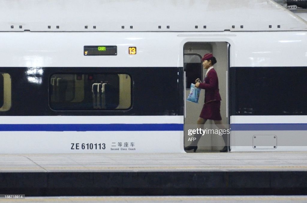 A stewardess walks inside a high-speed train running from the Beijing to Guangzhou, south China's Guangdong province, at the Beijing west railway station in Beijing on December 26, 2012. China on December 26 started service on the world's longest high-speed rail route, the latest milestone in the country's rapid and sometimes troubled super fast rail network.