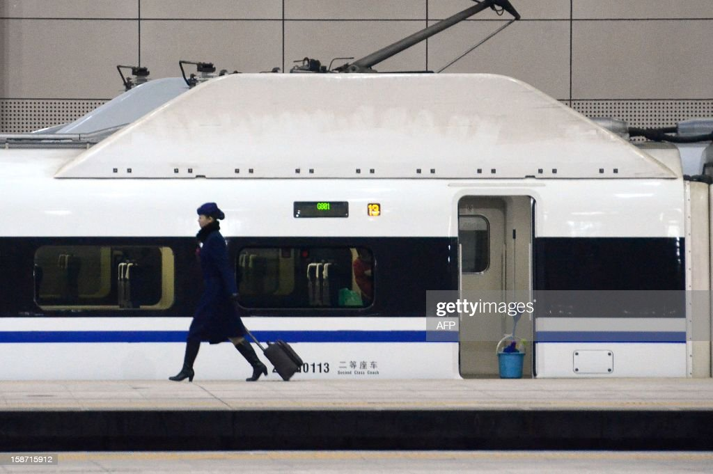 A stewardess walks past a high-speed train running from the Beijing to Guangzhou, south China's Guangdong province, at the Beijing west railway station in Beijing on December 26, 2012. China on December 26 started service on the world's longest high-speed rail route, the latest milestone in the country's rapid and sometimes troubled super fast rail network.