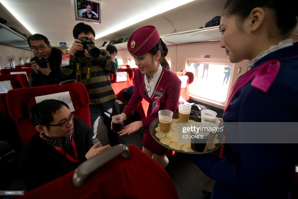 Stewardesses offer tea to journalists aboard a high-speed train in Hebei province south of Beijing on December 22, 2012. China showed off the final link of the world's longest high-speed rail route, set to open on December 26, stretching from Beijing to the southern Chinese city of Guangzhou. Travelling at around 300 kph, trains on the new route are expected to cover the 2,298-kilometre (1,425-mile) journey in a third of the current time from 22 hours to eight. AFP PHOTO / Ed Jones