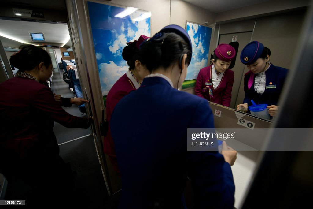 Stewardesses pour tea for journalists aboard a high-speed train in Hebei province south of Beijing on December 22, 2012. China showed off the final link of the world's longest high-speed rail route, set to open on December 26, stretching from Beijing to the southern Chinese city of Guangzhou. Travelling at around 300 kph, trains on the new route are expected to cover the 2,298-kilometre (1,425-mile) journey in a third of the current time from 22 hours to eight. AFP PHOTO / Ed Jones