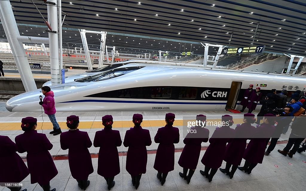 Stewardesses stand beside a CRH high-speed train at Beijing West Railway Station on December 26, 2012 in Beijing, China. The world's longest high-speed rail route linking Beijing and Guangzhou started operation on Wednesday. Running at an average speed of 300 kilometers per hour, the 2,298-kilometer new route will cut the travel time between Beijing and Guangzhou from more than 20 hours to around eight.