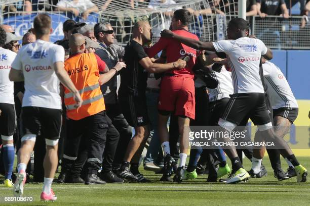 Stewards and Lyon staff members try to stop Bastia's supporters who invade the pitch to fight with Lyon players during warm up prior to the French L1...