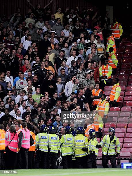 Stewards and police stand in front of the West Ham United fans during the Carling Cup second round match between West Ham United and Millwall at...