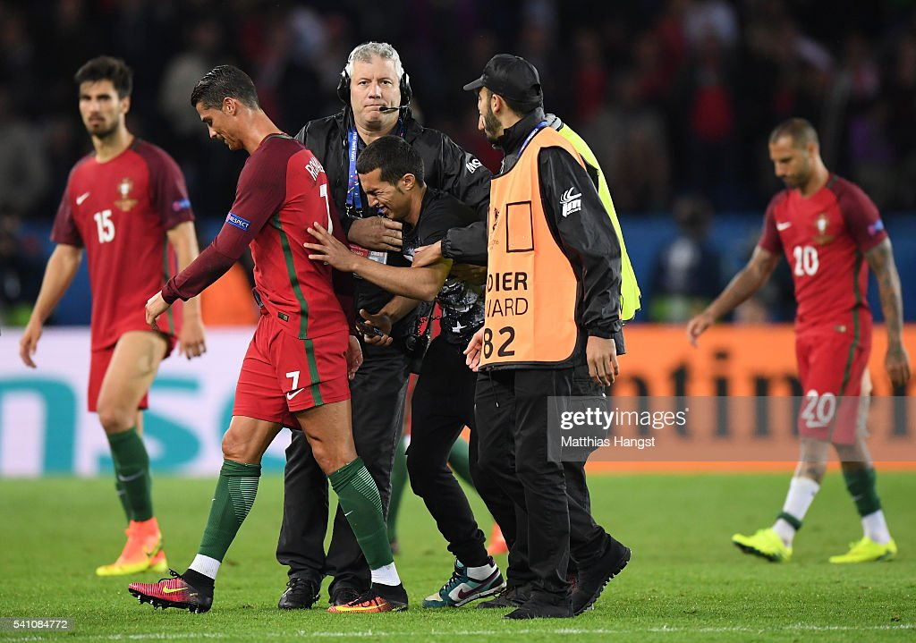 Stewards carry an emotional fan off the pitch as he attempts to reach Cristiano Ronaldo of Portugal during the UEFA EURO 2016 Group F match between Portugal and Austria at Parc des Princes on June 18, 2016 in Paris, France.