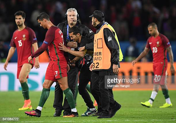 Stewards carry an emotional fan off the pitch as he attempts to reach Cristiano Ronaldo of Portugal during the UEFA EURO 2016 Group F match between...