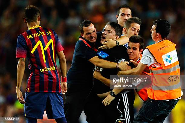 Stewards hold a fan who tried to hug Neymar of FC Barcelona during a friendly match between FC Barcelona and Santos at Nou Camp on August 2 2013 in...