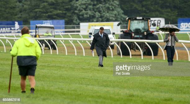 Stewards inspect the track after a heavy downpour prior to the running of Sportsbet's New Racing Form BM64 Handicap at SportsbetBallarat Racecourse...