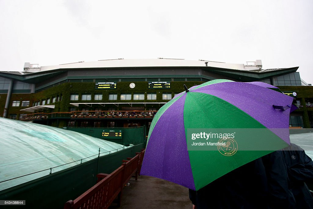 Stewards shelter under an umbrella as rain delays play during day two of the Wimbledon Lawn Tennis Championships at the All England Lawn Tennis and Croquet Club on June 28, 2016 in London, England.