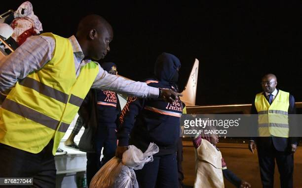 Stewards show the way to Ivorian migrants disembarking from a plane upon arrival from Libya to be repatriated in their country at the airport of...