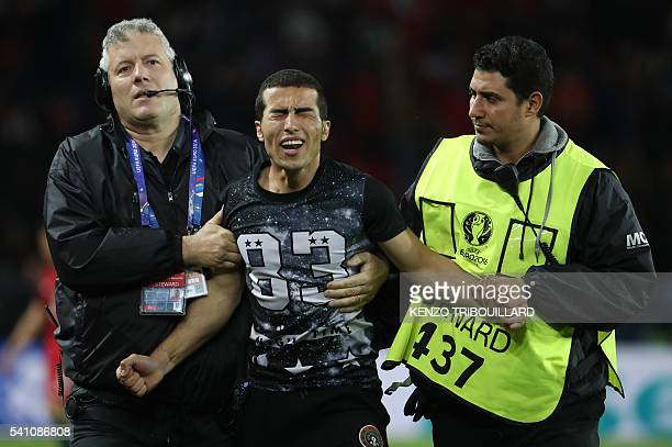 TOPSHOT Stewards take a fan out of the pitch after greeting Portugal's forward Cristiano Ronaldo at the end of the Euro 2016 group F football match...