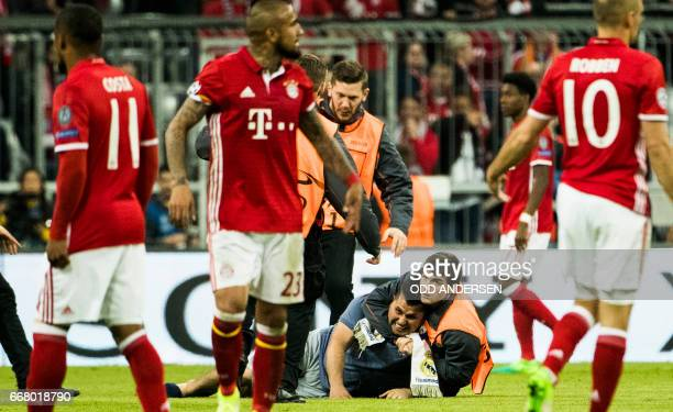 Stewards wrestle a pitch invader to the ground during the firstleg quarter final Champions league football match between Bayern Munich and Real...