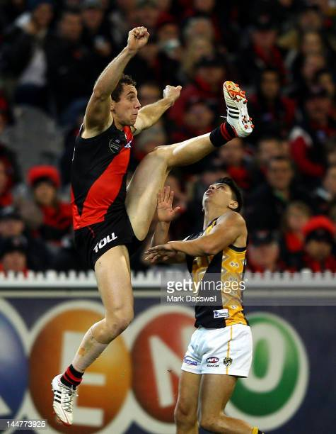 Stewart Cramer of the Bombers leaps over Robin Nahas of the Tigers during the round eight AFL match between the Essendon Bombers and the Richmond...