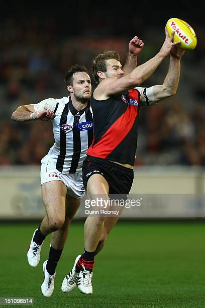 Stewart Crameri of the Bombers marks infront of Nathan Brown of the Magpies during the round 23 AFL match between the Essendon Bombers and the...