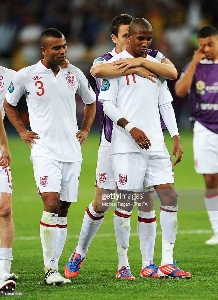 Stewart Downing of England comforts Ashley Young of England as Ashley Cole of England looks on during the UEFA EURO 2012 quarter final match between...