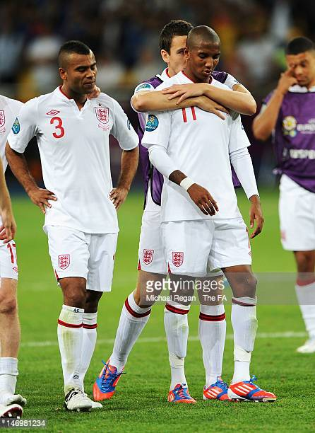 Stewart Downing of England comforts Ashley Young of England as Ashley Cole of England looks on during the UEFA EURO 2012 quarter final match between...