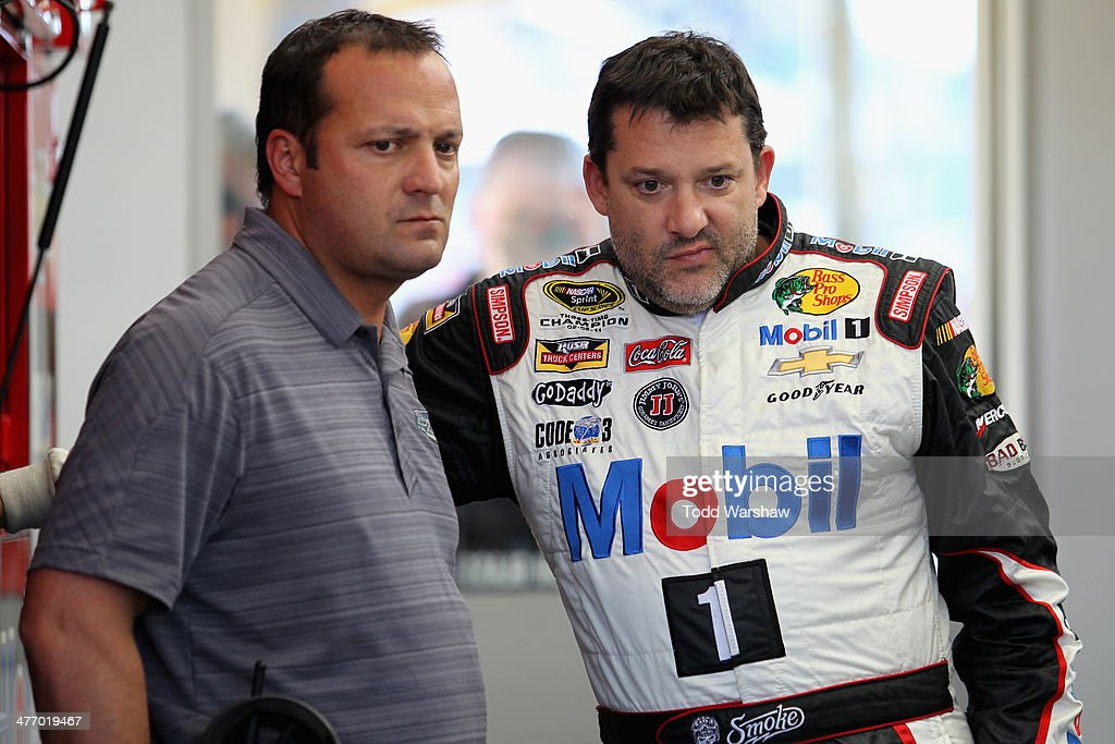 Stewart-Haas Racing competition director <a gi-track='captionPersonalityLinkClicked' href=/galleries/search?phrase=Greg+Zipadelli&family=editorial&specificpeople=559825 ng-click='$event.stopPropagation()'>Greg Zipadelli</a> talks to <a gi-track='captionPersonalityLinkClicked' href=/galleries/search?phrase=Tony+Stewart+-+Race+Car+Driver&family=editorial&specificpeople=201686 ng-click='$event.stopPropagation()'>Tony Stewart</a>, driver of the Mobil 1/Bass Pro Shops Chevrolet, in the garage during a testing session at Las Vegas Motor Speedway on March 6, 2014 in Las Vegas, Nevada.
