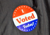 A sticker is stuck on a Washington DC resident's jacket after he cast his votes at a polling place in Washington DC on April 3 2012 Voters in...