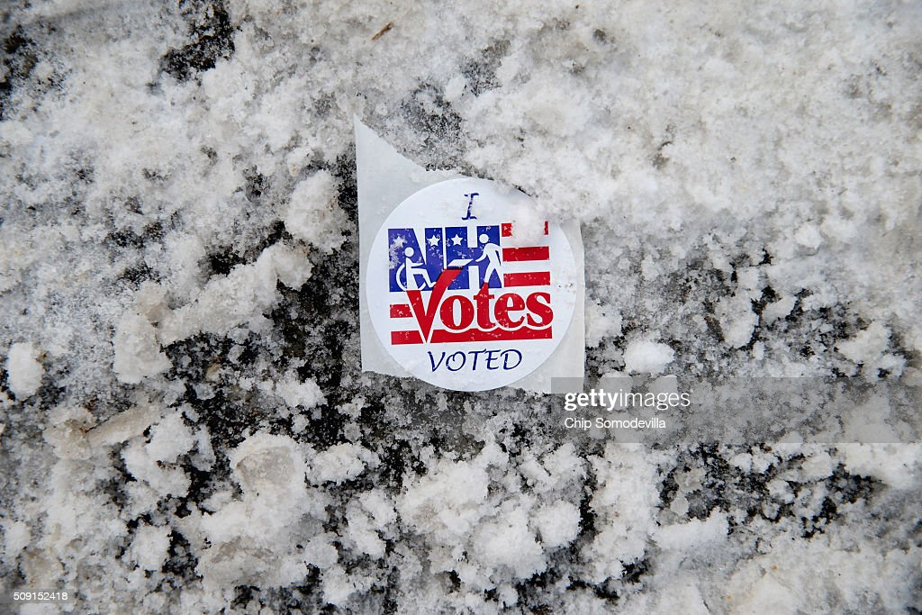 A sticker lies in the snow outside the polling place at the Webster School February 9, 2016 in Manchester, New Hampshire. Tuesday is the 100th anniversary of the New Hampshire primariy, the 'First in the Nation' test for presidential candidates from both parties.
