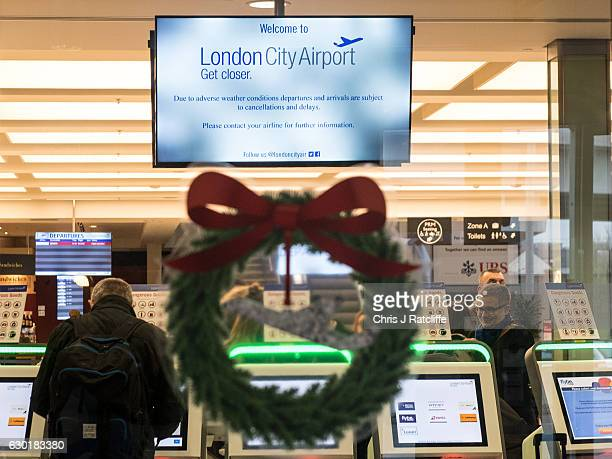 A sticker of a Christmas wreath and airplane on an entrance door to London City Airport as passengers check in and a sign above warns of delays and...